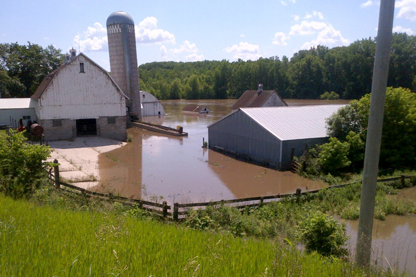 A farm yard is almost completely flooded with brown water from nearby river.