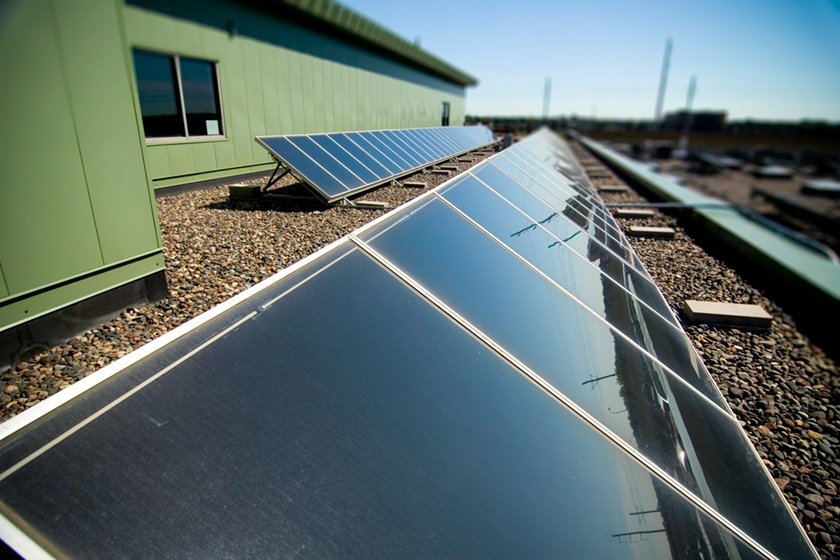 Close up of a photovoltaic or PV array stretching away across a roof top.