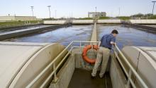 Wastewater treatment operator looking into treatment pond
