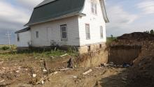 House next to pit dug in the ground