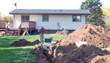 Backyard of home being dug up for a new septic system