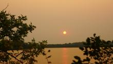Smoky air over a lake that is dimming light from the sun and making the scene look brown.