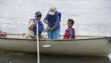 Three people in a boat doing water monitoring on Lake Harriet