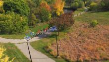 A bicycle sculpture forms a gateway to a paved trail that runs through colorful trees next to a river