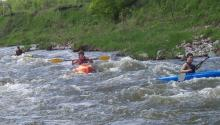 Three kayakers on river rapids
