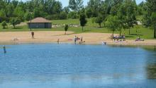 View from the lake looking toward people in the distance on a sandy beach and wading in the water.