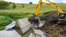 A yellow excavaor breaks up and removes a small concrete dam in a small stream