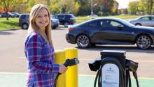A smiling woman standing next to a electric vehicle charging station, holding the charging cord