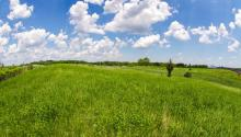 Green grassy hill and blue sky with fluffy white clouds at the Twin Cities Army Ammunition Plant federal Superfund site.