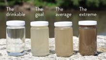 4 jars show clear tap water on the far left, and three samples from the Minnesota River that are light brown, medium brown, and dark brown.