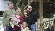Two generations of the Jennissen family standing in a dairy barn