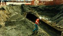 workers in big hole removing combined sewer pipe