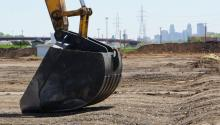 Steam shovel digging soil on a brownfield site