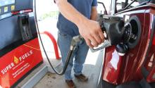 Man fueling up red vehicle at gas pump.