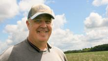 Close up of smiling white man in gray t-shirt and dusty cap standing in field.