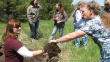 Woman holds out clump of soil for another woman to touch during discussion of soil health.