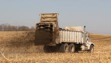 truck spreading manure on harvested crop field