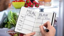 Closeup of hands holding a marker and a notebook with meal plan grid in front of an open refrigerator.