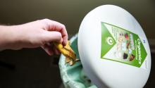 A hand places a banana peel into a plastic organics for composting bin