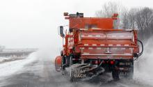 View from behind an orange snow plow truck throwing salt on a snowy road