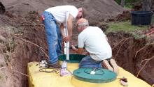 Two men installing white pipes into top of a septic system.