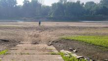 A boat ramp leads to a dry river bed. A man stands on the dry ground looking at the river in the distance.