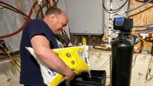 Man pours salt into water softener system in basement.