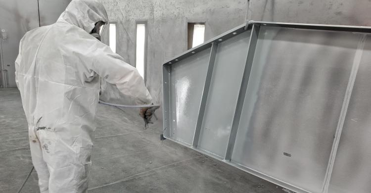 Person using a sprayer to apply paint