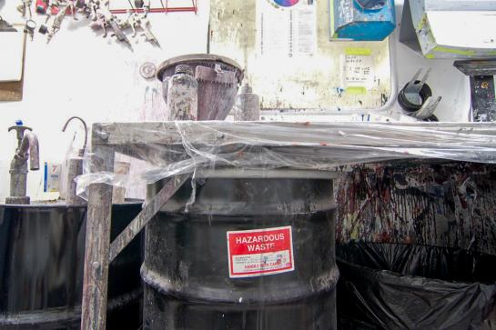 A black 50 gallon drum marked hazardous waste under a paint mixing table in an auto body shop