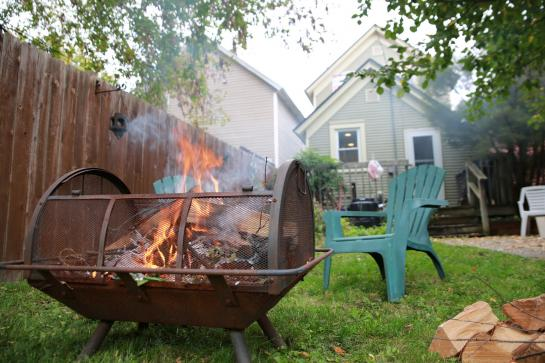 Green lawn chairs face smoky fire pit in backyard