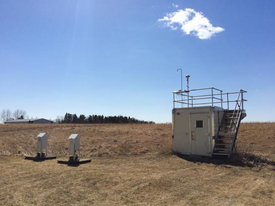 Small shed with air monitoring equipment on roof sits in field of brown grass.