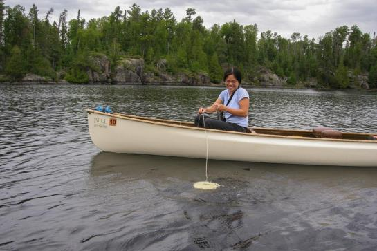 Woman sitting in canoe on lake surrounded by pine trees lowers a flat white disk into the water by a string