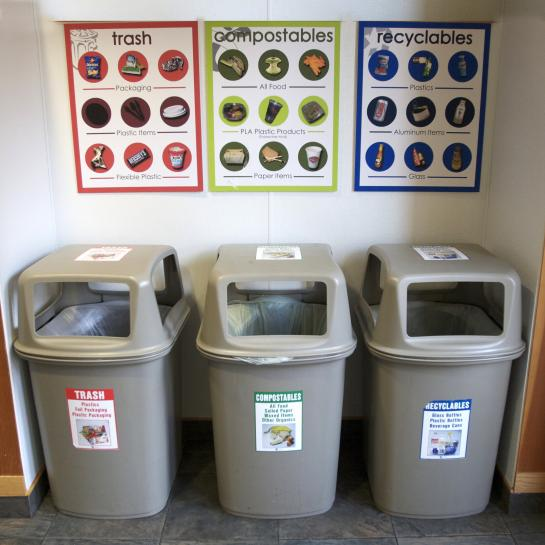 recycling bins and signs for trash, compostables, and recyclables