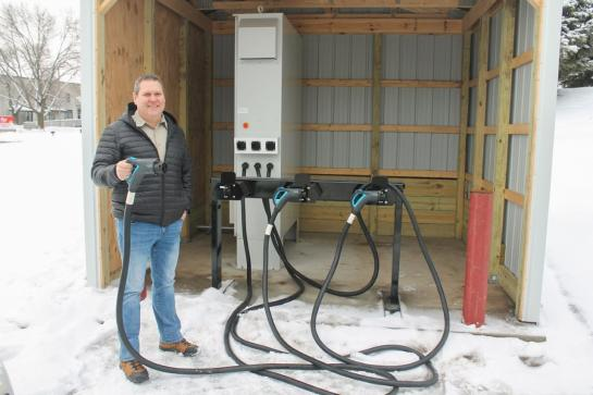Man in a black puffer jacket stands outside on a winter day next to an EV charging station. He is holding one of the chargers in his hand.