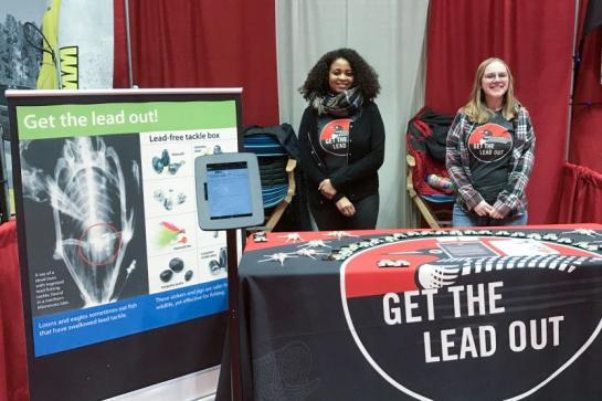 "Two women stand behind table and poster displaying ""Get the lead out"" information."