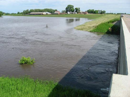 Brown water floods a field next to a highway. A farm is in the distance.