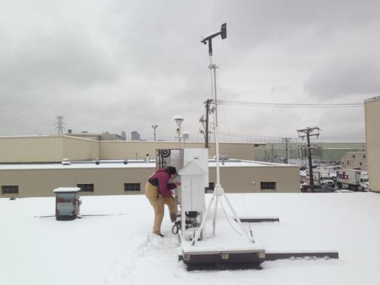 Person looks at monitoring equipment in white utility boxes on snow covered rooftop.