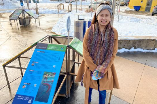 A young Hmong woman stands next to exhibit signs.