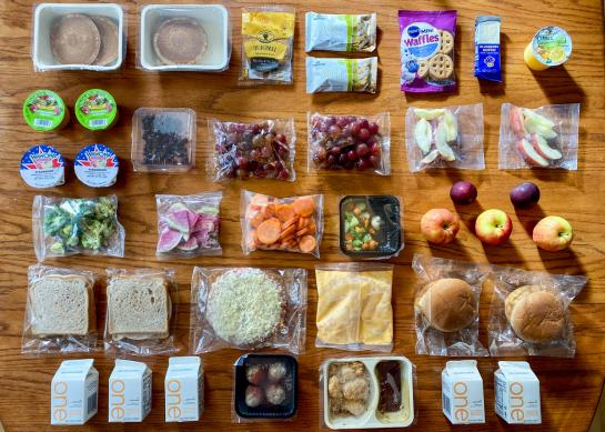 Packages of sandwiches, hamburgers, fruit, vegetables, pancakes, bars, and juice arranged in a grid on a table.