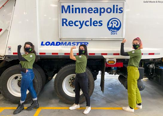 Three women flexing biceps of right arm stand in front of recycling truck with sign that reads Minneapolis Reycyles.