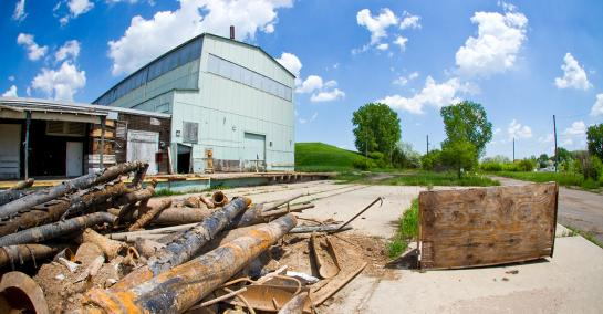 A pile of rusted black metal pipes on the ground with an abandoned corrugated metal building in the background