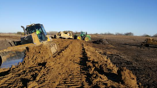 Earth-moving equipment creating a berm of dirt