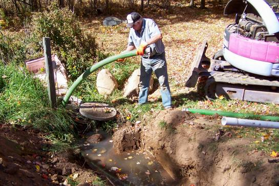 A man feed a large green hose into the opening of a septic system.