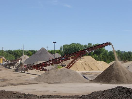 A red conveyor belt pours gravel on top of a large mound.