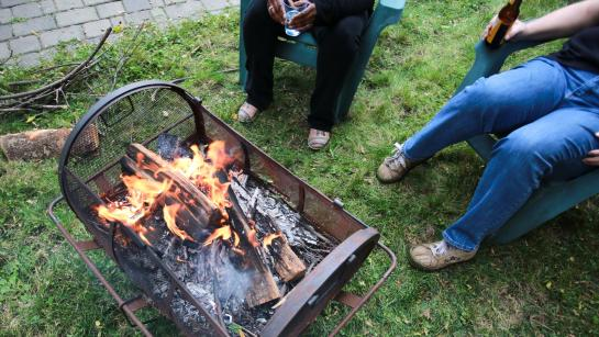 Flames and smoke come from burning wood in a metal firepit in a backyard