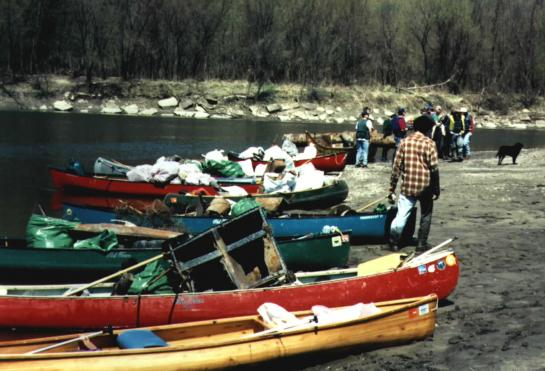 Canoes on a river bank piles with trash
