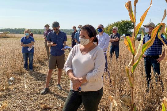 A dark-haired woman wearing a light gray sweater and a face mask stands in a farm field with a group of people and listens attentively.