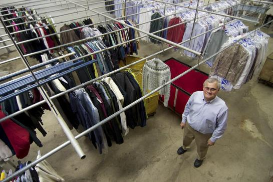 Man stands by rows of sweaters and shirts hanging from ceiling rack at dry cleaner.