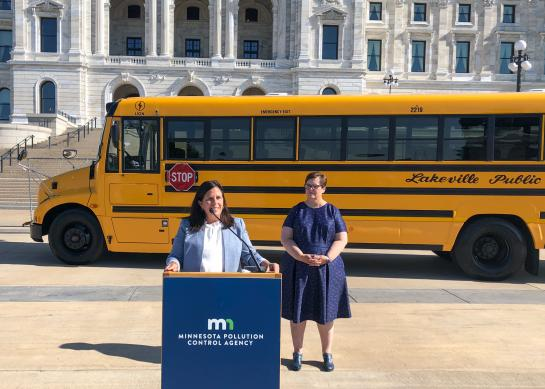 Commissioner Laura Bishop making an announcement in front of the Minnesota State Capitol building with an electric school bus parked behind her.