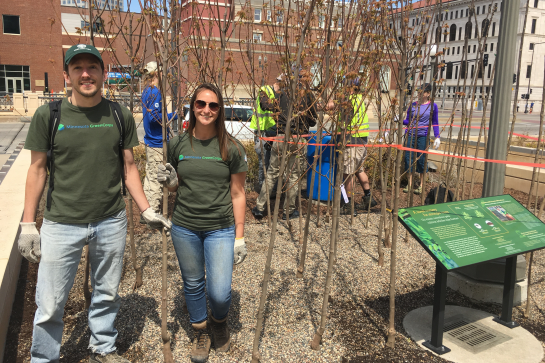 Minnesota GreenCorps members show off trees ready to be transplanted from the gravel bed nursery at the Science Museum of Minnesota.